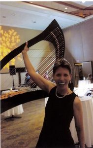 Harpist Anne Roos lifts her harp with one hand