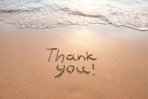 Thank you, written in the sand on the beach